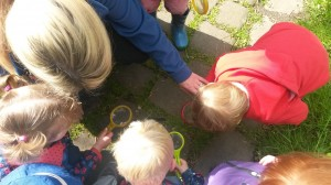 Image of children looking through magnifying glasses at the path